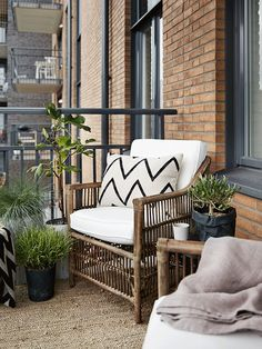 Beautiful wooden balcony chairs with white patterned cushions