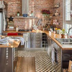 Cozinha estilo industrial, com armários em inox e parede de tijolinhos.