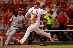 St. Louis Cardinals' Matt Adams, right, scores on a three-run double by Jhonny Peralta as Cincinnati Reds starting pitcher Johnny Cueto stan...