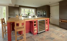 Red island unit with Oak stools, work top, wine rack and tray details.