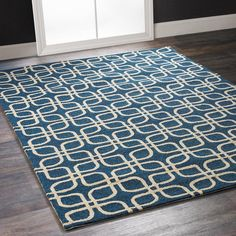 Navy Symmetry Indoor Outdoor Rug Enjoy rhythm in blues with graphic symmetry in ivory on navy. The classic blue and white color combination in loop pile is a good foundation for dining, den or deck in easy care hand hooked polypropylene with special treatment to resist UV and moisture damage. Available in accent and room size rugs, including 8' round.