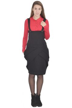 Black pinafore with cleavage to under the bust. The straps of the pinafore are with buttons. The skirt of the model has shallow tucks. The pinafore is long to the knees and has nuts for a belt.