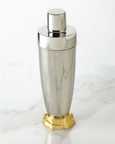 """Handcrafted cocktail shaker. Made of stainless steel and gold-tone metal. Hand wash. 10""""T. Imported."""