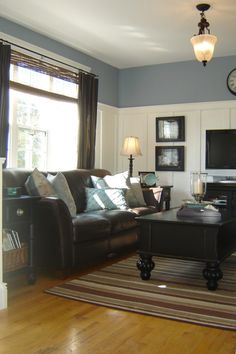 Blue walls in Pikes Peak Gray by Benjamin Moore with brown couch - family room