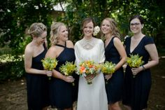The bride & bridesmaids holding their gorgeous bouquets of oranges & yellows.