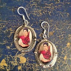 These alpaca or nickel silver backed earrings have the oval image of Frida Kahlo, covered in a matte resin. The pieces that go into the earlobe are sterling. Frida Kahlo, a Mexican icon, is one of the most beloved mortal women EVER! She appears almost everywhere.3 pairs available There are several