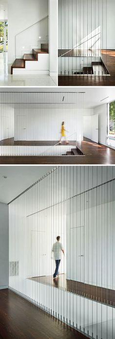 Tre dekket trapp fører opp til andre etasje i denne moderne hus, med vertikale kabler som gir en sikkerhet rekkverk for den åpne trappeoppgangen.