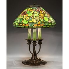 Rare Tiffany Studios New York Leaded Glass Geranium Table Lamp - Shade signed Tiffany Studios New York. With three arm bronze and art glass candlestick base. Base signed Tiffany Studios New York 580. Stained glass table lamp.