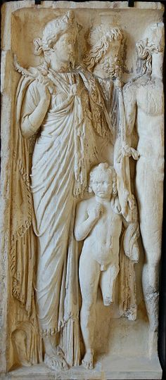 Isis, Serapis and their child Harpocrates (Louvre Museum). Isis (on the left, holding a sistrum), Sarapis (wearing a modius), the child Harpocrates (holding a cornucopia) and Dionysos (holding the thyrsus). Marble relief, last quarter of the 2nd century CE, found at Henchir el-Attermine, Tunisia.