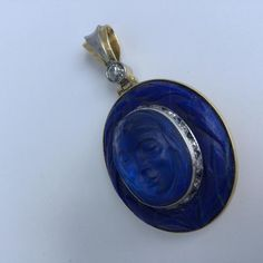 Karl Faberge Solid Platinum/18K Gold Lapis Dual-Tiered Cameo Pendant W/Mine-Cut Blue Sapphire & Mine-Cut Diamonds - This investment quality piece is made of solid platinum and 18K gold. The pendant displays dual tiered carved lapis. The bottom layer appears to be the hair of a woman, and the center of the pendant is raised and has a woman's face. The woman's face is raised off of the piece, and is lined with platinum. The platinum lining is embelished with mine cut diam...