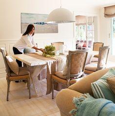 Mujer poniendo la mesa en comedor beige. Comedor en tonos claros con sillas de un estilo clásico