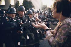 """""""La Jeune Fille à la Fleur"""", la foto di Marc Riboud mostra la giovane pacifista Jane Rose Kasmir piantare un fiore sulle baionette delle guardie al Pentagono durante una protesta contro la guerra del Vietnam il 21 ottobre 1967."""