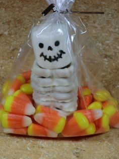 Use an edible marker for the face, and white chocolate coated pretzels stacked for the body.  Cute!    http://www.thriftyfun.com/Halloween-Treat-Bag-Ideas.html