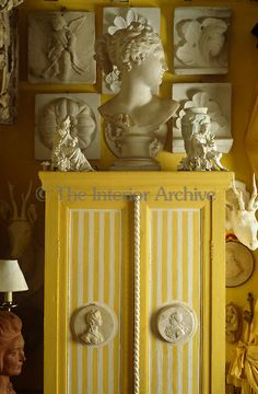 Casts of architectural details cover the walls of the living room and a Greek bust and figurines sit on top of a yellow and white striped cabinet ~ Normandy, France.