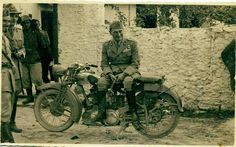 Italian Army officer sitting on a Bianchi motorcycle 250cc. Location should be in Albania or Greece