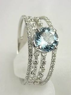 A set of four diamond bands combined to make a gorgeous ring with a round shaped aquamarine at the center .  since aquamarine is my birthstone and diamond is my favorite stone i think this should be my ring .