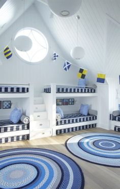 Children's bedrdoom. Built in bunk beds. Blues and whites - stripes. Flags hanging from ceiling.