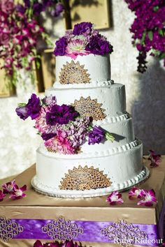 A white and purple wedding cake for an Indian wedding reception.
