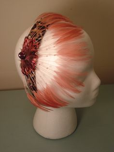 Pink Cheetah. This handmade treasure can be worn two ways! Featuring pink beaded feathers on a cheetah band with a lace jewel accent, wear it forward for old-time class or backward for rocker chic! $25.00 (plus tax)