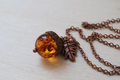 Here is a darling little acorn necklace featuring an Amber bead in an antiqued copper acorn top. ♥ Lucite/man made amber ♥ The Acorn measures at