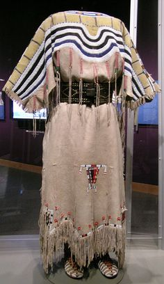 Blackfoot Two Hide Dress.    Circa 1860, Canada. With belt (1900) and moccasins (1890.) Dress made of hide, pony beads, glass trade beads, seed beads, black and yellow paint, blue and red wool and sinew. Belt made of harness leather, brass tacks, buckle. Moccasins made of hide, rawhide, seed beads, red wool, blue cotton and sinew.