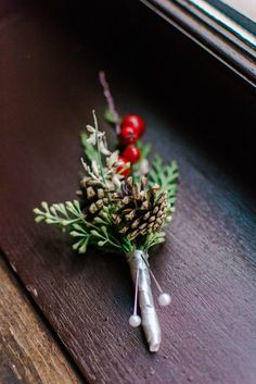 A perfect holiday-time wedding boutonniere with holly berries and pine cone - what a great idea! | The Yuletide Bride inspiration shoot by Belles & Beaux and Sarah Elizabeth Photography featured on Richmond Wedding Collective, see more at richmondweddingcollective.com