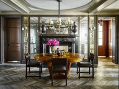 A French oak table is paired with 1950s chairs by Jules Wabbes and a circa-1950 French chandelier in the dining room; églomisé mirrors, framed in cerused oak, surround an 1830s marble fireplace, and the chevron floor is antique fumed oak.    - ELLEDecor.com