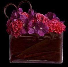 """Ovando's """"Valentine Coquet"""" features ruffles of beautifully plush ranunculus and carnations are accented with purple orchids. Finished with a leaf-wrapped vase and heart-shaped dogwood, this composition is wonderfully coquettish."""