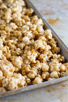 An easy recipe for homemade caramel popcorn – made from a simple brown sugar caramel, and then baked until perfectly crispy. This caramel corn is perfect for family movie night at home! Caramel Corn Recipes, Popcorn Recipes, Popcorn Favors, Popcorn Bowl, Popcorn Snacks, Candy Recipes, Baking Recipes, Snack Recipes, Dessert Recipes