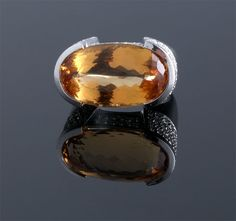 OVAL IMPERIAL TOPAZ AND DIAMOND RING. THE APPROXIMATELY 15.00 CARAT TOPAZ RING ALSO HAS AN ESTIMATED 1.80 CARATS OF DIAMONDS SET IN 18KARAT GOLD (23 X 13MM)