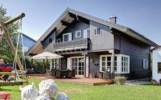 Das Referenzhaus, ganz traditionell im österreichischen Stil entworfen, mit Alpenland-Atmosphäre und dezent rustikal, wurde hier denn auch in wesentlichen Punkten verändert und präsentiert sich in einem aktualisierten Look. Die anthrazitfarbene Fassade, weiße Untersichten, Fenster, Sprossen und Klappläden, die farbliche Betonung der sichtbaren Sparren -das alles wirkt frisch und zeitgemäß. Auch zeitgemäß: Die Twinligna-Klimawand, eine patentierten Eigenentwicklung von Sonnleitner. Das… Mansions, House Styles, Outdoor Decor, Home Decor, Exposed Rafters, House With Granny Flat, Roof Styles, House Numbers, Floor Layout