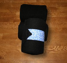 """Equine Polo Wraps/Black Polo Wraps w/Periwinkle Vines Velcro Strap Made with quality fleece and industrial strength velcro to ensure a proper hold. Two sizes offered: Pony: 2 yards (6ft) length, 4"""" wide Horse: 9 ft front, 11 ft hind length, 5"""" wide."""