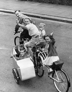 "Jewell Family (1950)   Mr Eric Jewell, of Dukes Avenue, Finchley, London, with his wife and children on a ""quinticycle"" - adapted from a tandem with sidecar. Here on a day by the Thames at Windsor. The Jewell Family, cycling, 1950"