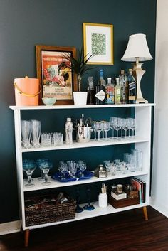 If you don't have a bar cart, don't sweat it. We love the convenience of converting a small bookcase into a well-stocked bar. There's a shelf for everything!  Source: Katie Kett for The Everygirl