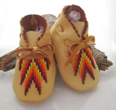 Beaded Baby Moccasins in a soft golden deerskin that allows for stretch and comfort. The bead work is a southwest pattern in yellow and reds on Etsy, $62.28 CAD