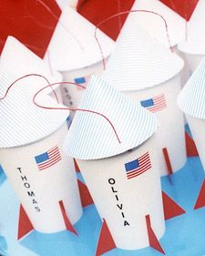 Favors Glue silver or striped paper to red paper; cut a 6 1/2-inch circle. Cut a triangle from the circle and shape it into a cone; tape. Punch holes in the sides of the cup and bottom of the cone. Thread string through the cup and cone; knot. Glue triangular red tabs to the cup for fins. Add flag stickers and names with stickers.