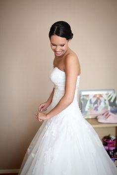bruid kijkt omlaag en lacht naar haar zusje
