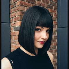 A precise bob with bangs in a deep, shiny shade of black never goes out of style. Image courtesy Chrome Hair Design salon. #AvedaColor