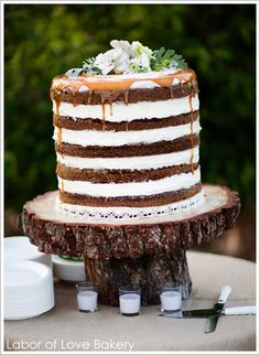 Layers of carrot cake and cream cheese icing stacked tall and topped with a drizzle of caramel.