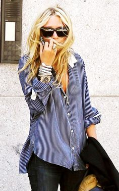 Mary-Kate Olsen wears a pinstriped boyfriend-style button-down shirt with silver and gold-toned accessories.