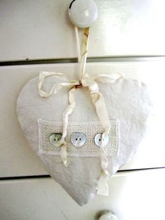 "his gorgeous sachet measures approximately 8x9"" and is stuffed with French organic lavender. It is embellished with shell buttons and a vintage stained ribbon. The fabric is a rumply, cozy cotton.  It smells so yummy!"
