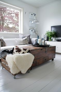 Living Space with a Cool oversized trunk on wheels coffee table with a crate filled with cozy pillows. Strøkent