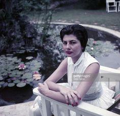 Rendezvous With The Princess Soraya Of Iran, Former Wife Of Shah Reza Pahlavi. Europe- Années 1960- Portrait de la Princesse SORAYA d'Iran, ex-femme du SHAH D'Iran, vêtue d'une robe blanche, assise dans un fauteuil installé dans un jardin, aux abords d'une mare fleurie de nénuphars.
