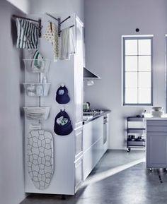 La parete laterale di un mobile alto della cucina, con cesti e binari per riporre il necessario per il bucato - IKEA