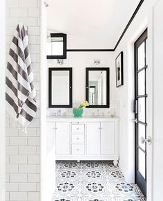 Modern black and white bathroom with graphic tiled floors and black window trim.