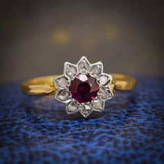This adorable #antique #flower ring pretty and striking at the same time, with unusual pointed (#sunflower-esque) petals and a fabulous central #ruby, of exceptional colour. The head is finished in #millegrain #platinum, and the band modelled in warm 18ct #gold. An attractive open gallery allows light to illuminate the stones from behind, adding yet more vibrance to the ruby. Online now at www.butterlaneantiques.com :) #antiquejewelry #flowerrings #butterlaneantiques #showmewyourrings…