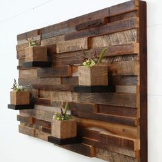 Rough scraps of wood are mounted onto a backing board. Larger boards glued and screwed in place are perfect for wood blocks drilled out with a spade or MAD bit for mini flower arrangements.