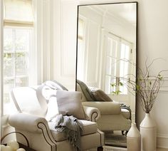 Oversized floor mirrors in the corner by a window will make any room look bigger and taller
