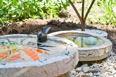 handcrafted bird baths, concrete, art glass, metal objects and/or other ornamentation   ...Looks like a great diy to me.