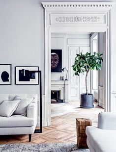 Living room with intricate moldings in bright whites and soft grays, modern art, and warm parquet floors